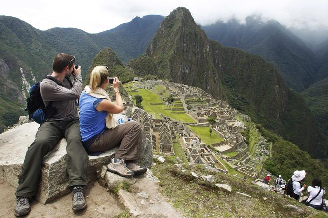 A tourist couple takes pictures of Inca's citadel of Machu Picchu in Cuzco